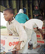 A boy unloads aid delivered by the French Air Force