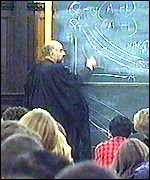 lecturer wearing gown writing on blackboard