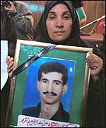 The sister of Ezzat Ibrahimnejad, killed in the July unrest, displays his photo at court