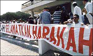 Demonstrators with banner: 'God Save Harakah'
