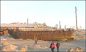 Children play in a ship cemetary in the Aral Sea
