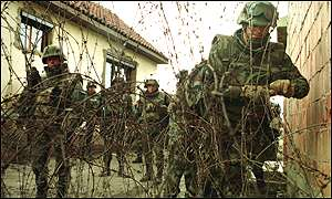 K-For peacekeepers put up barbed wire in Mitrovica