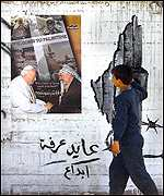 Palestinian boy views poster showing Arafat and Pope