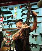A gun shop owner inspects a weapon