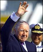 Augusto Pinochet waves to supporters upon his recent return to Chile