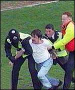 [ image: A Barnsley fan is led away after a pitch invasion]