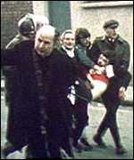 [ image: Civilians carry away the wounded on Bloody Sunday in 1972]
