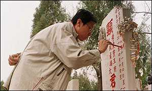 image: [ A Chinese man paints the inscription on his parent's grave north of Beijing ]