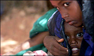 An Ethiopian girl holds a child at a feeding center in Gode