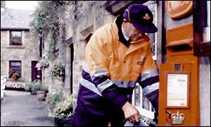 Postman emptying postbox
