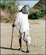 A man carries home a small pot of drinking water after a five mile walk