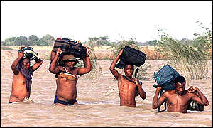 People carry bags through the flood waters