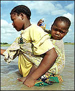 Woman carries baby through the flood