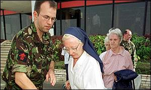 A British soldier helps a nun at Dakar airport