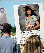 A marcher carries a sign with a picture of a victim