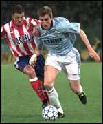 [ image: Lazio's Alan Boksic (right) holds off an Atletico defender]