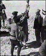 [ image: British soldiers searching Arabs during the revolt in the late 1930s]