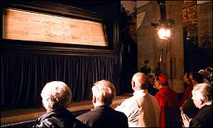 image: [ Some of the faithful gather to look at the shroud shortly after it was put on display in Turin Cathedral ]