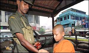 Monk ties string on soldier's arm