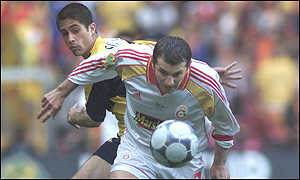 Galatasaray's Okan Buruk and Arsenal's Silvinho clash