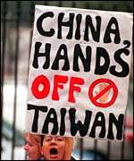 A protestor carries a sign decrying China's stance towards Taiwan