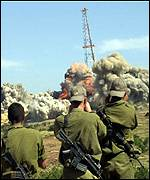 Israel troops watch outpost being blown up