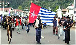 Demonstrators carry Free West Papua banned flag