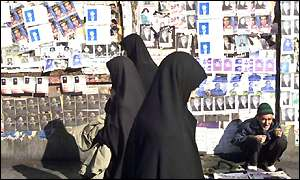 Iranian women walk past election posters