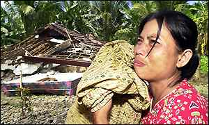 A woman cries in front of her house in Manna