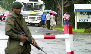 An armed Fiji military soldier patrols a roadblock, in the captial Suva