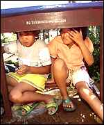 Children shelter under a table