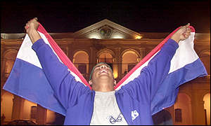An anti-Oviedo demonstrator holds a Paraguayan flag around himself