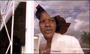 Independent MP Margaret Dongo looks out from her vandalised window