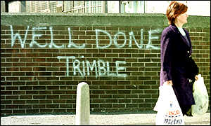 image: [ A woman walks past grafitti in support of the Ulster Unionist leader on the Shankill Road, west Belfast ]