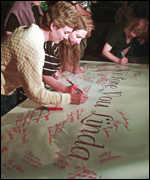 [ image: Mourners sign a giant condolence card]
