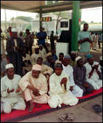 [ image: A group of Nigerian Muslims conduct an impromptu prayer session at a petrol station]
