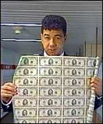 Nick Bryant holds up a sheet of dollar bills
