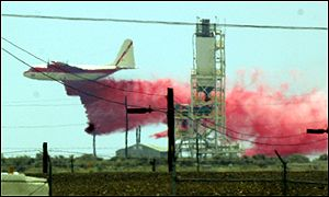 A plane drops chemical fire retardant on the facility