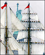 Tall ship sails past the statue of liberty