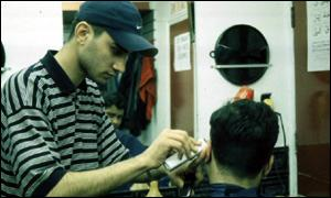 A hairdresser cuts a young man's hair