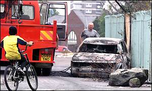 A burnt-out car lying on a Belfast street