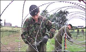 Soldiers put razor wire in place in fields at Drumcree