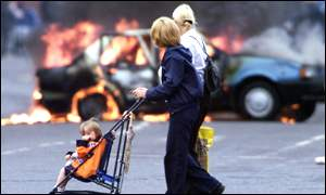 Women and children make their way past a burning vechicle in Belfast city