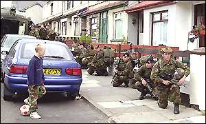 A child watches soldiers crouching in a nationalist area of Portadown
