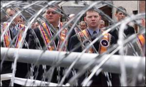 Orangemen on the march beside razor wire at Drumcree