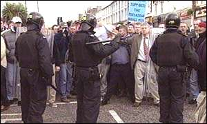Riot police hold back a large loyalist crowd at Lurgan