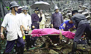 Firemen remove the body of a landslide victim