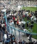 Football fans flood onto the pitch