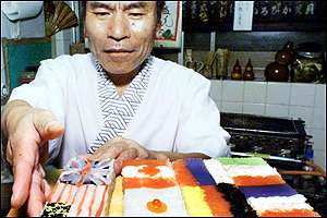 Man prespares sushi in G8 flags
