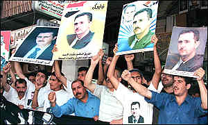 Syrians holding up posters of Bashar outside parliament after his swearing-in